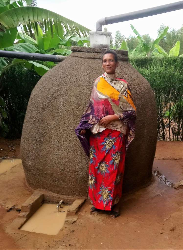 Muturinde and her rainwater harvesting tank